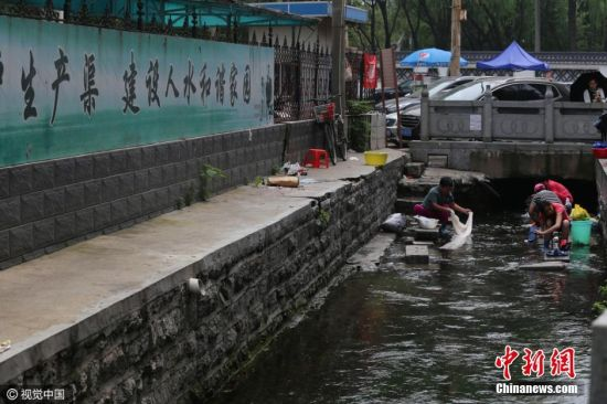市民在该河道内洗衣服,涮拖把