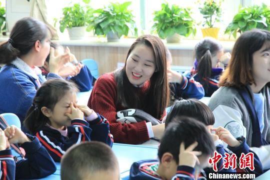 图为留学生在饶有兴趣地观看小学生做眼保健操. 沙见龙 摄
